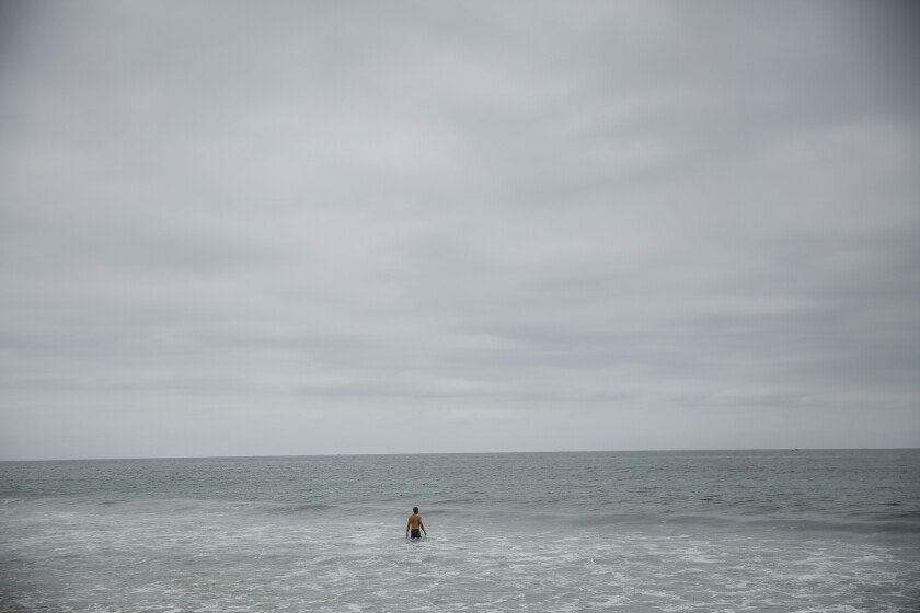 A man wades into the surf in Hermosa Beach under overcast June skies in 2018.