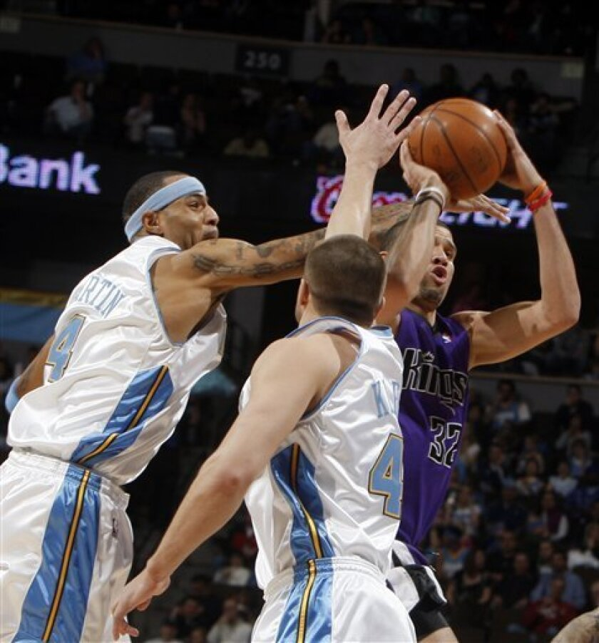 Sacramento Kings forward Francisco Garcia, right, of the Dominican Republic, shoots a 3-point basket and draws a foul from Denver Nuggets forward Kenyon Martin, left, as forward Linas Kleiza, of Lithuania, comes in to cover as time runs out in the first quarter of an NBA basketball game in Denver o