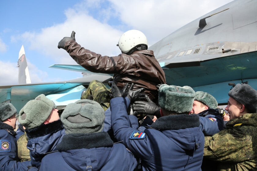 A Russian pilot receives a hero's welcome on returning from Syria at an airbase near the Russian city of Voronezh on Tuesday in a photo provided by the Russian Defense Ministry Press Service.