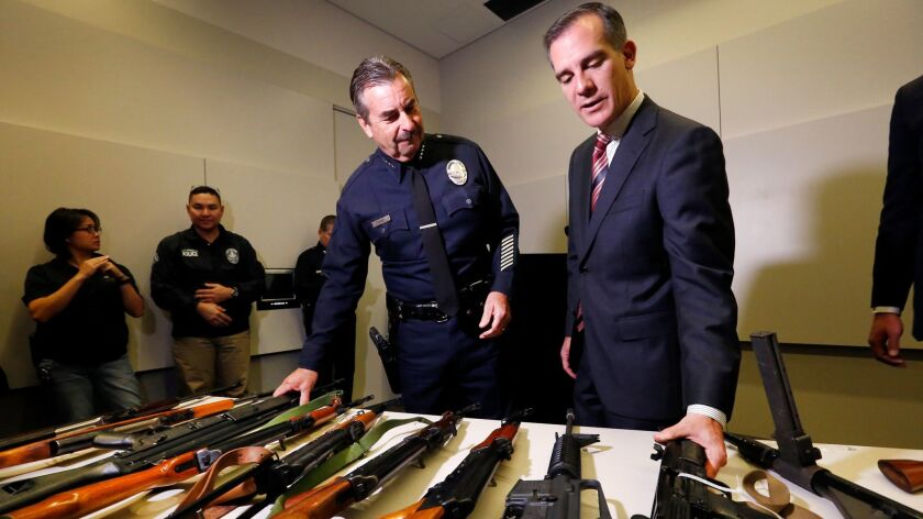 LAPD Chief Charlie Beck, left, and Mayor Eric Garcetti get a close look at some of the weapons colle