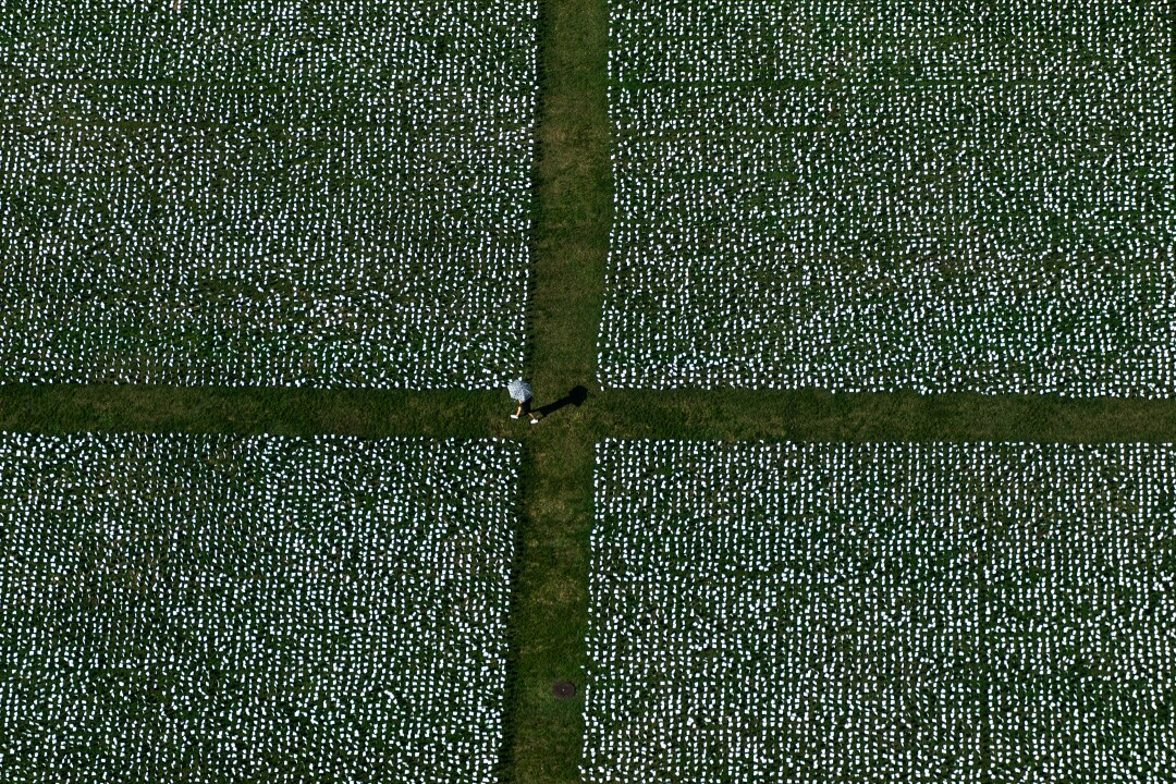 A person stands at the corner of four blocks of white flags in the grass, seen from above