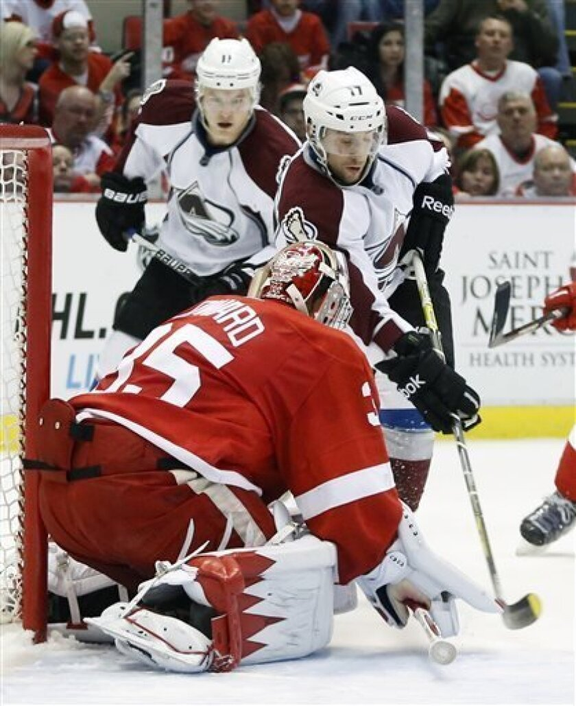 Colorado Avalanche right wing Aaron Palushaj, right, tries to get a shot against Detroit Red Wings goalie Jimmy Howard (35) as Colorado Avalanche left wing Jamie McGinn, left, watches in the first period of an NHL hockey game Monday, April 1, 2013, in Detroit. (AP Photo/Duane Burleson)