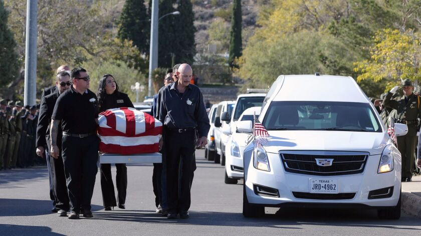 Pallbearers carry Border Patrol agent Rogelio Martinez into Our Lady of Guadalupe Church for a funer