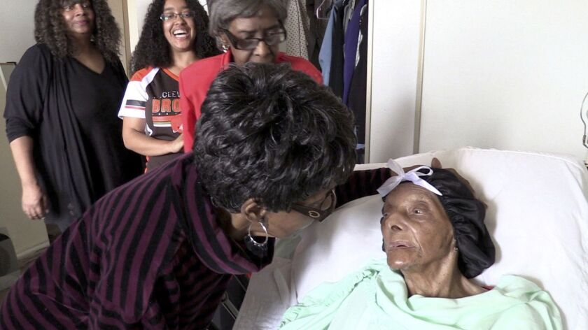 Lessie Brown is visited by her daughters, Verline Wilson, foreground, and Vivian Hatcher, third from left, and other family and friends at her home in Cleveland Heights, Ohio, on Sept. 22, 2018. Brown, believed to be the oldest person in the United States, died Tuesday.