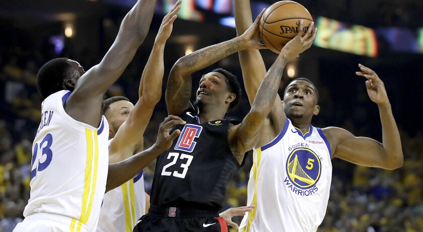 Clippers guard Lou Williams draw three defenders while attempting a shot during Game 1 on Saturday in Oakland.