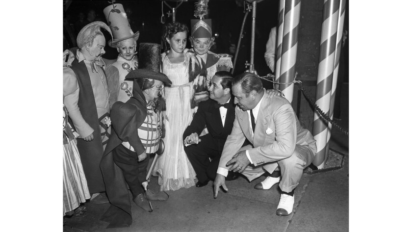 """Aug. 15, 1939: Surrounded by Munchkins from the """"Wizard of Oz,"""" Carrol Ann Beery enjoys forecour"""