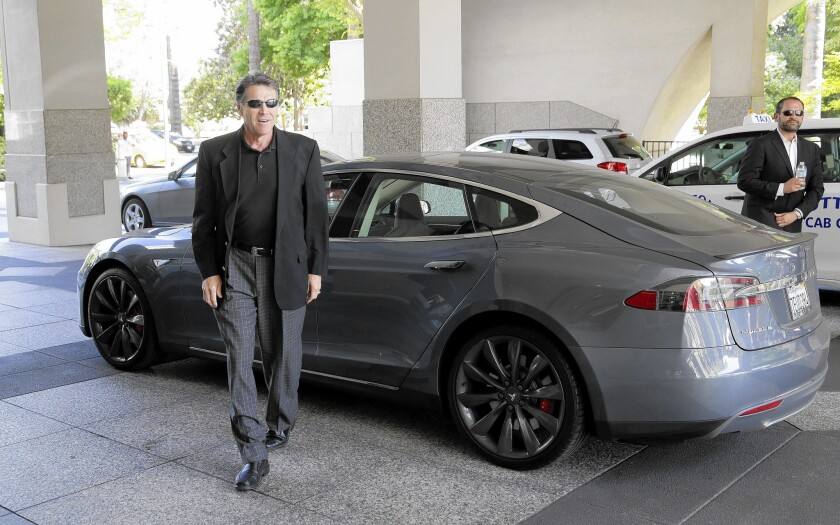Texas Gov. Rick Perry walks over to talk to reporters Tuesday after driving up in a Tesla Model S electric car in Sacramento. Perry said he'd like to add Tesla to a high-profile list of businesses that have relocated facilities to the Lone Star State.