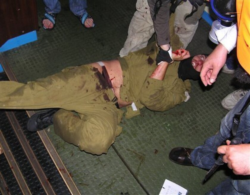 """In this Monday, May 31, 2010, photo taken by an unidentified person aboard the ship Mavi Marmara, an Israeli soldier is surrounded by people aboard the Turkish-flagged vessel. The photo was released by the Turkish activist group IHH, which is outlawed in Israel. According to IHH, the Israeli soldiers were hurt while storming the ship in confrontations with activists aboard, and were later returned to other Israeli troops who boarded the ship. Israel's military said the series of images """"shows that our boarding party in fact did face deadly violence from the hardcore Islamist activists on the boat from the fundamentalist IHH movement."""" (AP Photo/IHH) THE ASSOCIATED PRESS IS UNABLE TO INDEPENDENTLY VERIFY THE AUTHENTICITY, CONTENT, LOCATION OR DATE OF THIS HANDOUT PHOTO; NO SALES"""