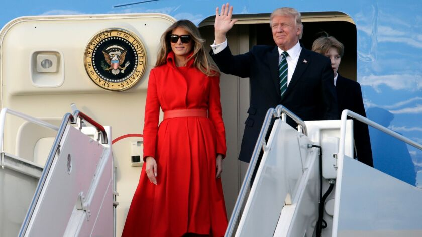 President Trump waves from Air Force One with First Lady Melania Trump and son Barron after arriving at the Palm Beach International Airport on Friday for a weekend at his Mar-a-Lago resort.