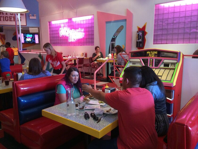 "In this Wednesday, June 1, 2016 photo, customers eat at pop-up restaurant Saved by the Max in Chicago. A vacant restaurant space in Chicago's Wicker Park neighborhood has become a replica of The Max, the fictitious hangout from the TV sitcom ""Saved by the Bell."" (AP Photo/Terry Tang)"