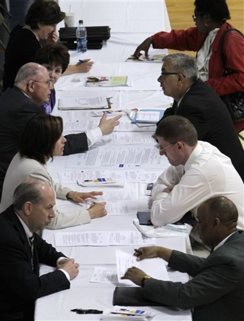 In this June 15, 2011 photo, job seekers, right, receive feedback on their resume's at a job fair in Southfield, Mich. More Americans applied for unemployment benefits last week, adding to evidence that the labor market is weakening. (AP Photo/Paul Sancya)