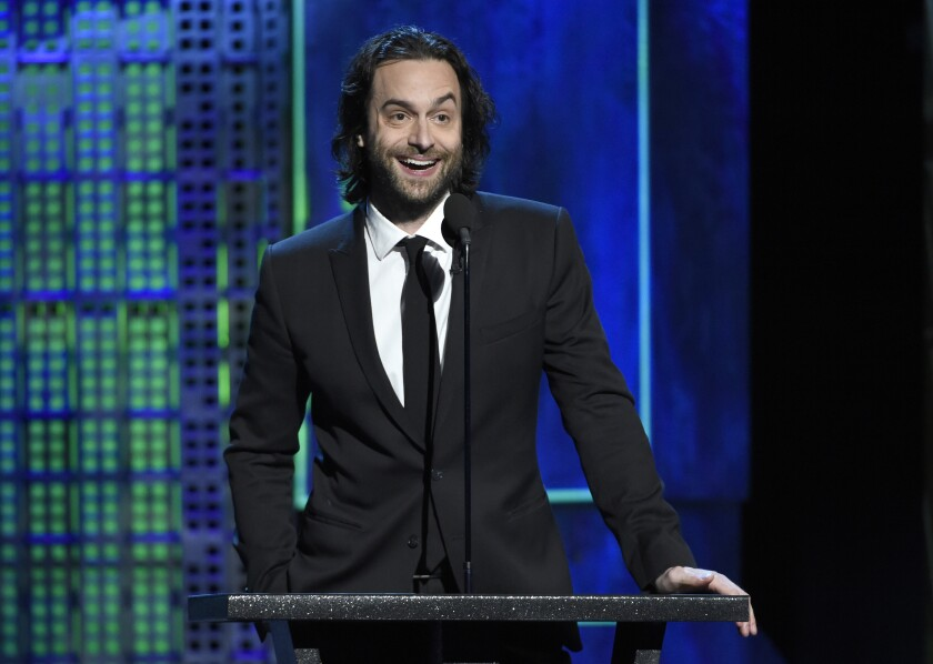 Chris D'Elia stands at a microphone wearing a dark suit