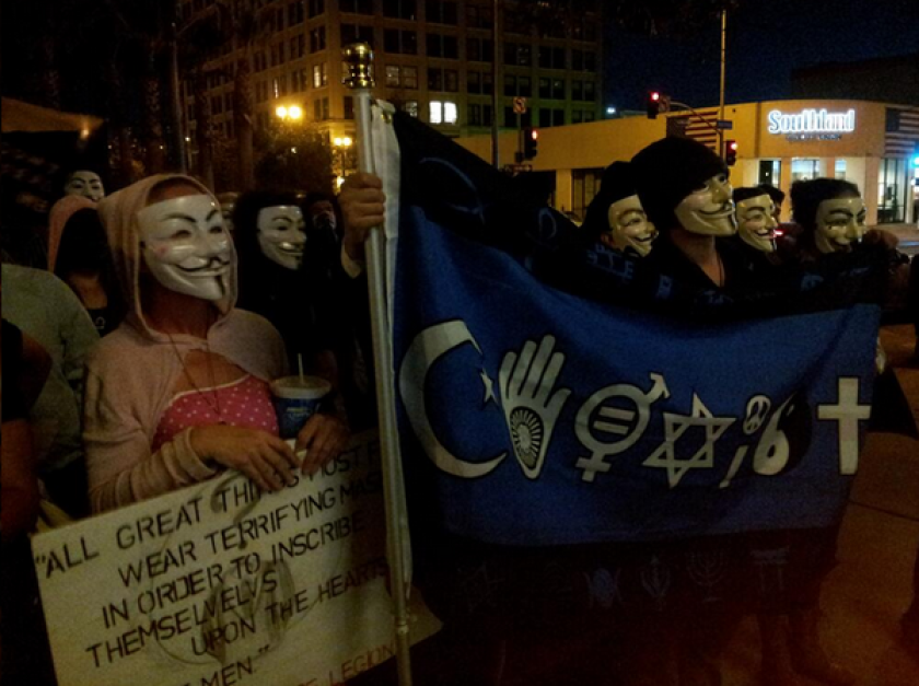 Members of the Anonymous Million Mask March gather at the L.A. Times building. In Colorado, 10 protesters were arrested after the Capitol was vandalized after their march.