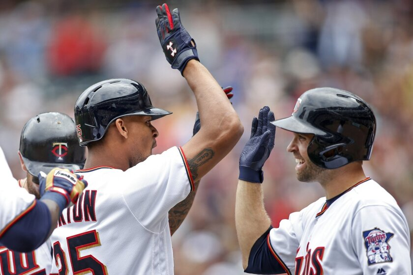 Minnesota Twins' Byron Buxton, left, celebrates with Brian Dozier after hitting a grand slam against the Chicago White Sox in the second inning of a baseball game Sunday, Sept. 4, 2016, in Minneapolis. (AP Photo/Bruce Kluckhohn)