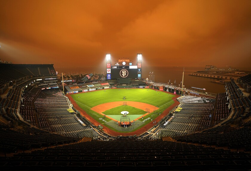 Smoke from wildfires obscures the sky over Oracle Park in San Francisco as the Seattle Mariners take batting practice before their baseball game against the San Francisco Giants on Sept. 9, 2020. (AP Photo/Tony Avelar)