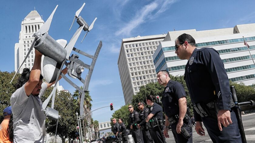Activist Miguel Guzman holds a drone replica in front of Los Angeles police officers after a small group of protesters blocked downtown traffic last fall to oppose the Police Commission's vote to allow the department to test the devices.