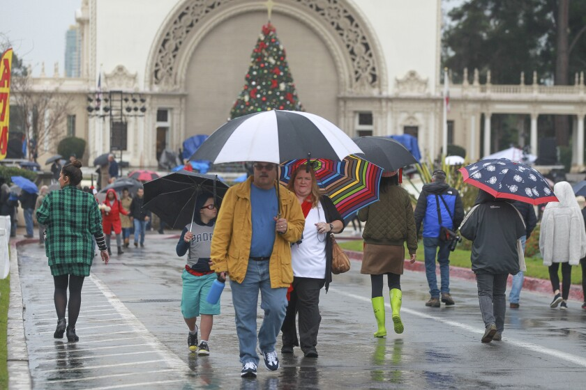 With the Spreckels Organ Pavilion in the background, people walk in the rain during the second day of December Nights at Balboa Park on Dec. 7. San Diego recorded 4.03 inches of rain in December, which was the city's wettest month of 2019.