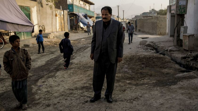 Col. Haji Habib Rahman, father of the slain Almar Habibzai, stands over the site where his son was killed outside their home in Kabul, Afghanistan.