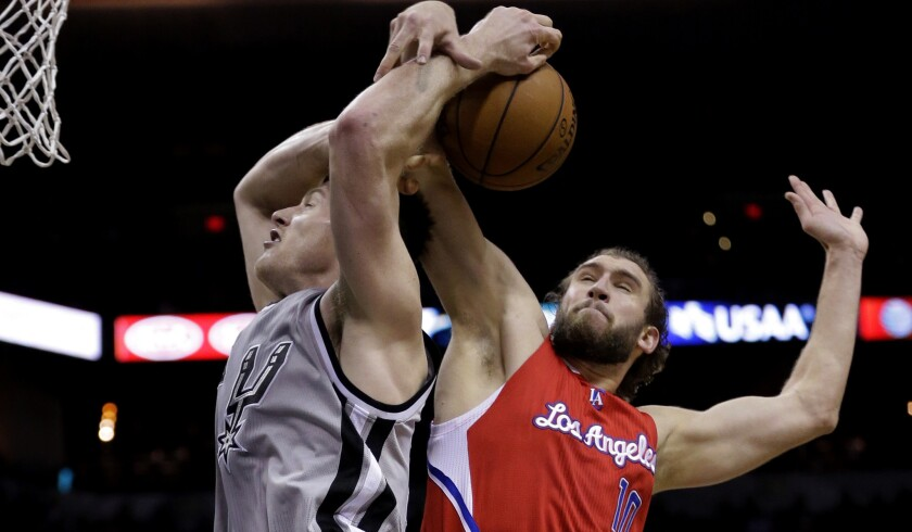 Spurs center Aron Baynes is fouled by the Clippers' Spencer Hawes in the second half Saturday night.