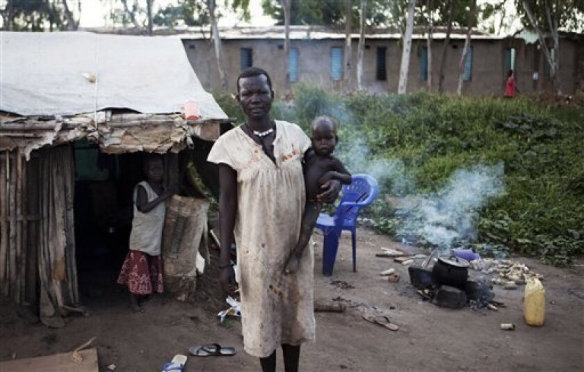 A woman from the Mundari tribe stands outside her makeshift home in Juba, southern Sudan on Wednesday, Aug. 18, 2010. The population of the defacto southern capital swelled considerably in recent years as those seeking employment or fleeing conflict and instability relocated to the city. Many set u