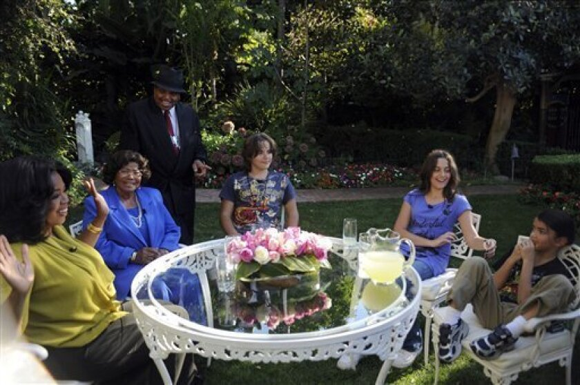 """In this photo taken Oct. 9, 2010 and provided by Harpo Productions Inc., talk-show host Oprah Winfrey, left, is seen with the Jacksons, during an interview with Katherine Jackson, second from left, mother of the late pop star Michael Jackson, in a taping of """"The Oprah Winfrey Show"""" in Encino, Calf. Looking on are Joe Jackson, Michael's father, and Michael's three children from left, Prince, Paris and Blanket. The show airs nationally Monday, Nov. 8, 2010. (AP Photo/Harpo Productions INc, Robin Slayton)"""