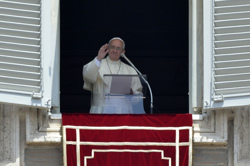 Pope Francis addresses the crowd from the window of his apartments during the Angelus prayer at St. Peter's Square on July 20.