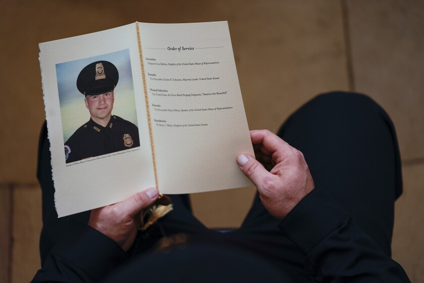 A U.S. Capitol Police officer holds a program during a ceremony memorializing U.S. Capitol Police officer Brian Sicknick.