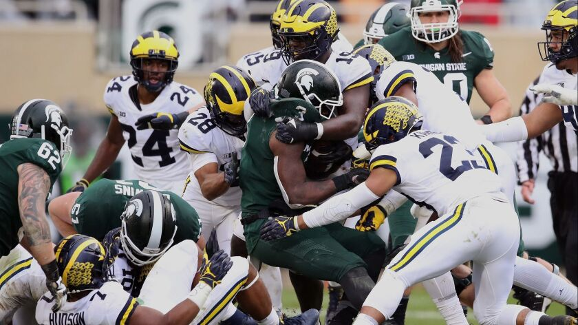Michigan State's LJ Scott is tackled by the Michigan defense during a second-half run at Spartan Stadium on Saturday in East Lansing, Mich. Michigan won the game 21-7.