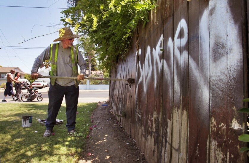 Escondido maintenance technician Dan Dorlaque works to remove graffiti from a wooden fence on East Mission Avenue. The fence has been hit by taggers many times.