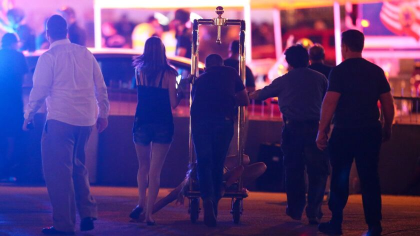 A wounded woman is moved outside the Tropicana during an active shooter situation on the Las Vegas Strip on Oct. 1..