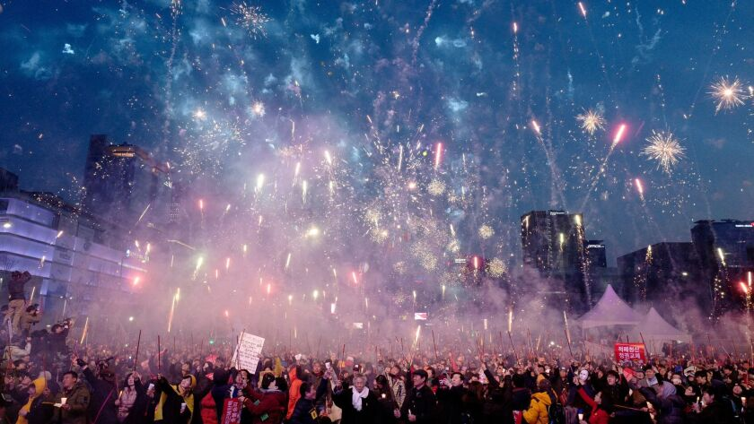 South Koreans release fireworks in central Seoul on March 11 as they celebrate after a court ruled on the impeachment of President Park Geun-hye.
