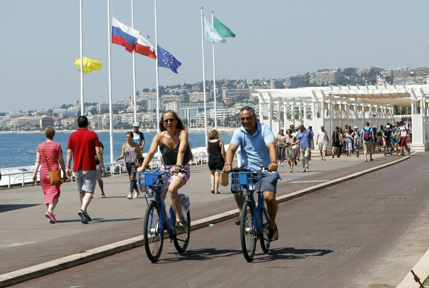 People ride bicycles along the Promenade des Anglais in Nice, southern France, Tuesday, July 19, 2016. Joggers, cyclists and sun-seekers are back on Nice's famed Riviera coast, a further sign of normal life returning on the Promenade des Anglais where dozens were killed in last week's Bastille Day truck attack. (AP Photo/Claude Paris)