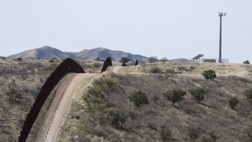A fence traces along the U.S-Mexico border near Nogales, Ariz.