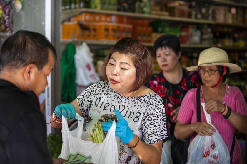 Yue Wa Market owner Amy Tran helps customers