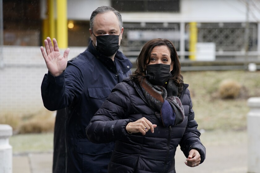 Kamala Harris and husband Doug Emhoff wave while walking outdoors