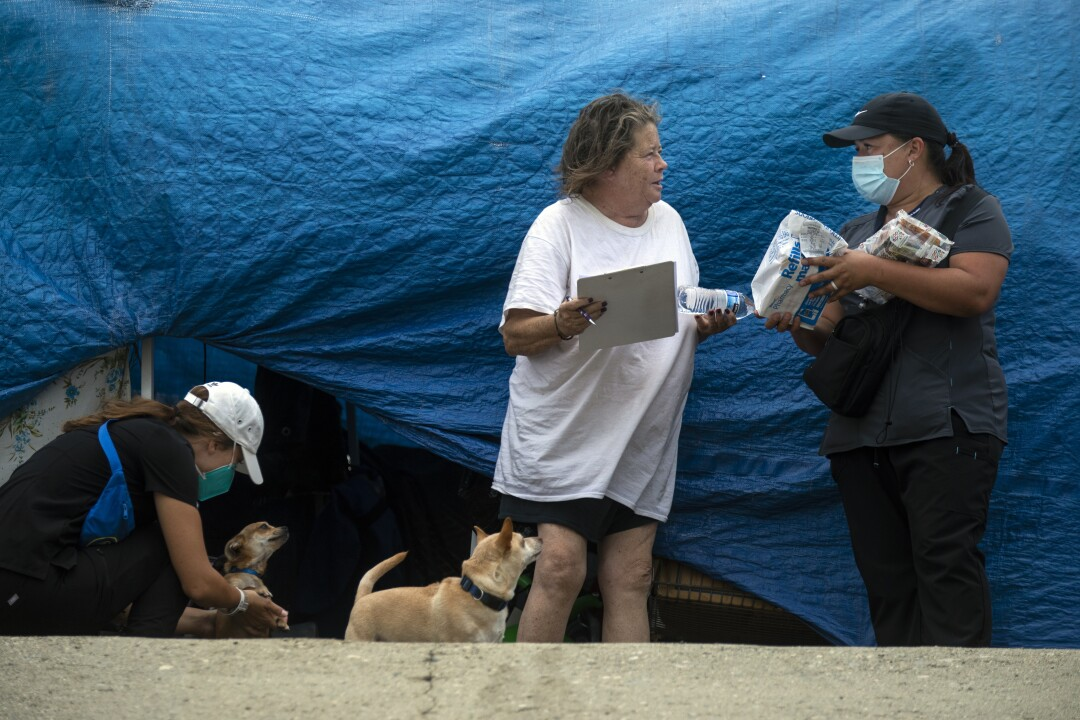 Members of the street medicine team talk to a homeless woman standing in front of blue tarps.