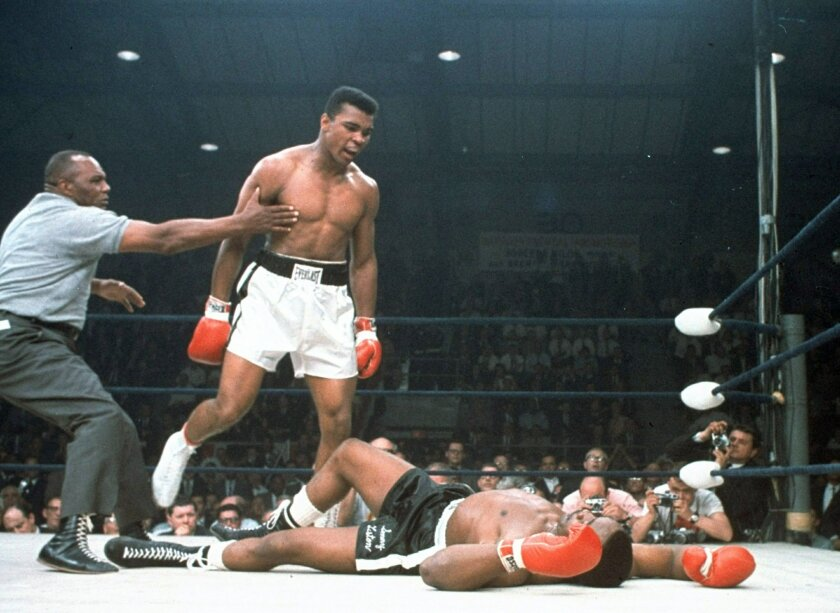 FILE - In this May 25, 1965, file photo, heavyweight champion Muhammad Ali is held back by referee Joe Walcott, left, after Ali knocked out challenger Sonny Liston in the first round of their title fight in Lewiston, Maine.  Ali, the magnificent heavyweight champion whose fast fists and irrepressib