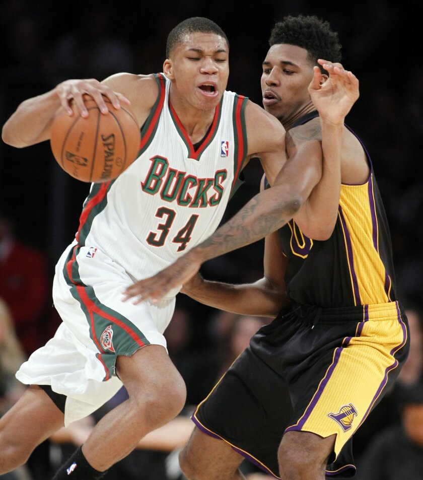Milwaukee Bucks guard Giannis Antetokounmpo (34) drives around Los Angeles Lakers forward Nick Young during the first half of an NBA basketball game Tuesday, Dec. 31, 2013, in Los Angeles. (AP Photo/Alex Gallardo)