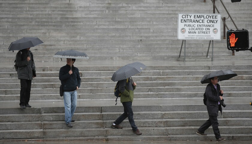 Visitors walk along the steps of City Hall as rain falls in downtown Los Angeles.