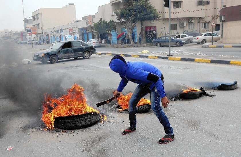 A protester sets tires ablaze during a demonstration last month in Tripoli, Libya.
