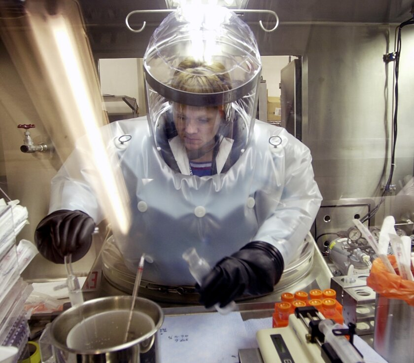 FILE - In this May 11, 2003, file photo, Microbiologist Ruth Bryan works with BG nerve agent simulant in Class III Glove Box in the Life Sciences Test Facility at Dugway Proving Ground, Utah. The specialized airtight enclosure is also used for hands-on work with anthrax and other deadly agents. The