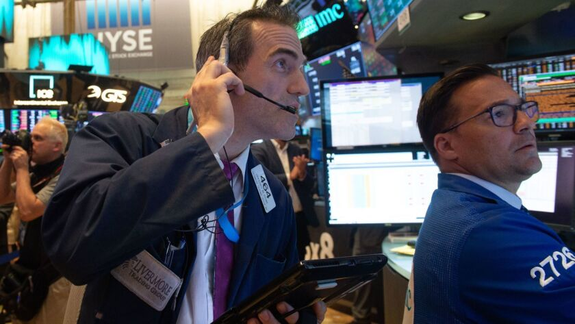 The Nasdaq composite index rose 55.93 points, or 0.7%, to a record-high 7,781.51 on Wednesday. Above, traders work on the floor of the New York Stock Exchange.