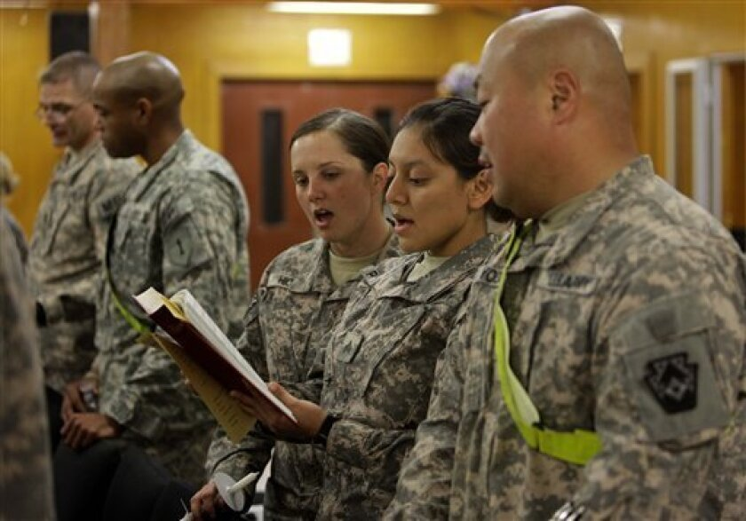 U.S. troops praying during a Christmas Eve mass in a chapel at an American military base in Baghdad, Iraq, Friday, Dec. 24,  2010. (AP Photo/Hadi Mizban)