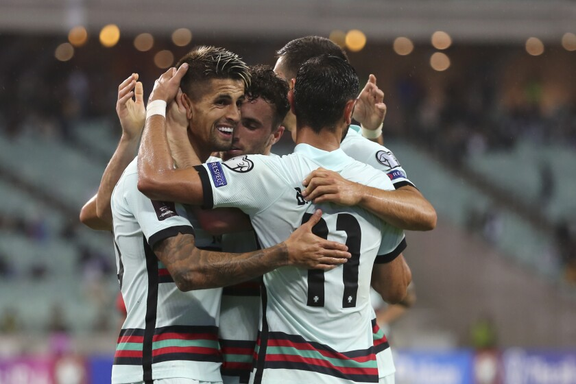 Portugal players celebrate after Portugal's Diogo Jota scored his side's third goal during the World Cup 2022 group A qualifying soccer match between Azerbaijan and Portugal at the Olympic stadium in Baku, Azerbaijan, Tuesday, Sept. 7, 2021. (AP Photo/Aziz Karimov)