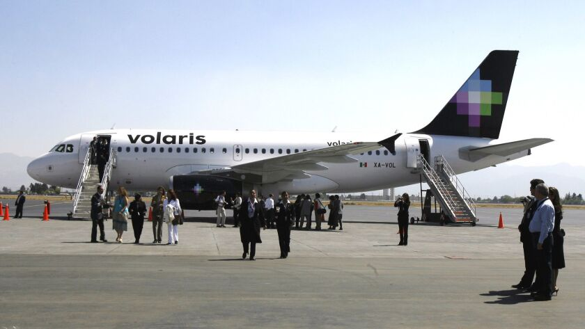 Visitors observe a Volaris airplane at the Ciudad de Toluca airport, Mexico, Monday, March 13, 2006.