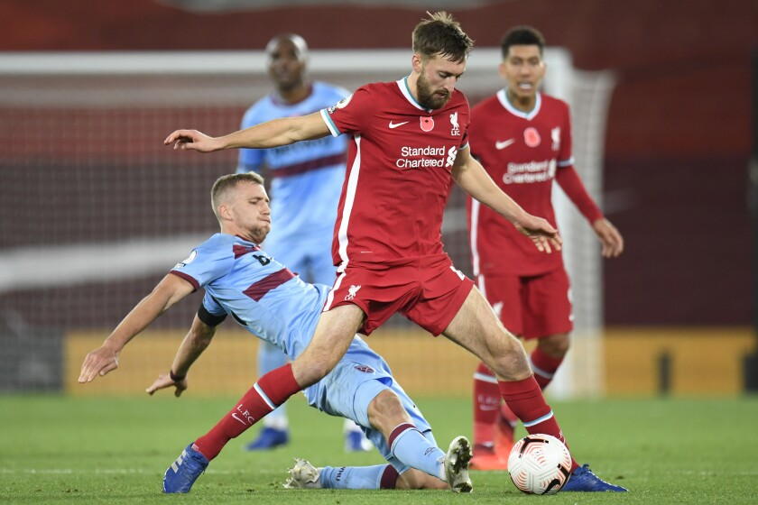 West Ham's Tomas Soucek, left, vies for the ball with Liverpool's Nathaniel Phillips during the English Premier League soccer match between Liverpool and West Ham United at Anfield stadium in Liverpool, England, Saturday, Oct. 31, 2020. (Peter Powell/Pool via AP)