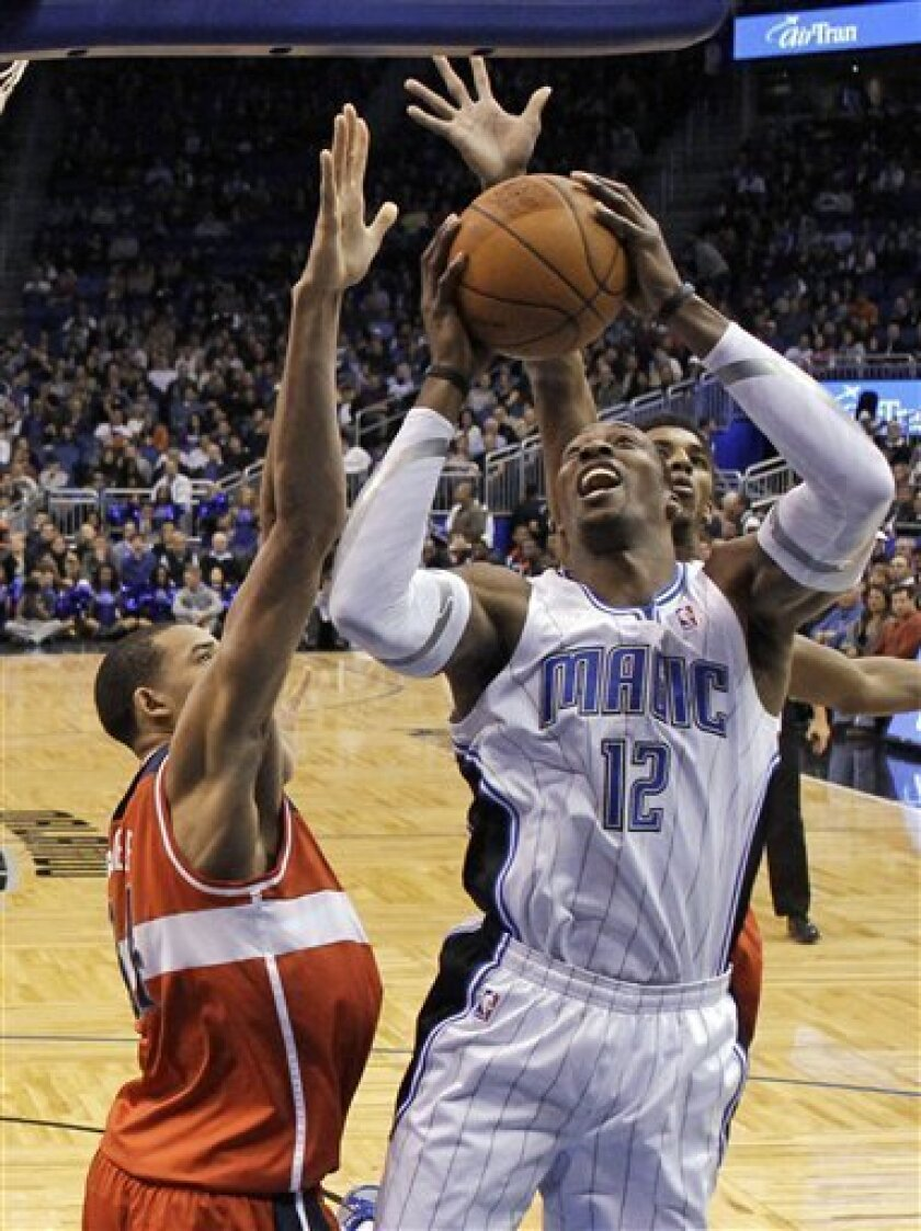 Orlando Magic center Dwight Howard (12) takes a shot under the basket in front of Washington Wizards' JaVale McGee, left, and Nick Young during the first half of an NBA basketball game Wednesday, Jan. 4, 2012, in Orlando, Fla. (AP Photo/John Raoux)