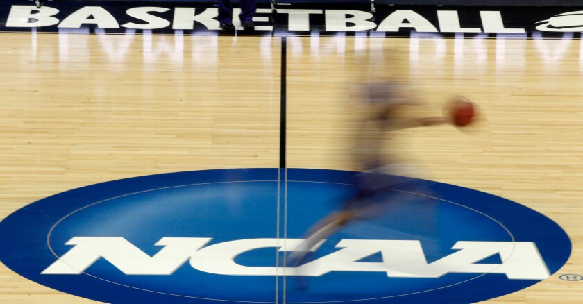 """FILE - In this March 14, 2012, file photo, a player runs across the NCAA logo during practice at the NCAA tournament college basketball in Pittsburgh. The NCAA Board of Governors took the first step Tuesday, Oct. 29, 2019, toward allowing athletes to cash in on their fame, voting unanimously to clear the way for the amateur athletes to """"benefit from the use of their name, image and likeness."""" (AP Photo/Keith Srakocic, File)"""