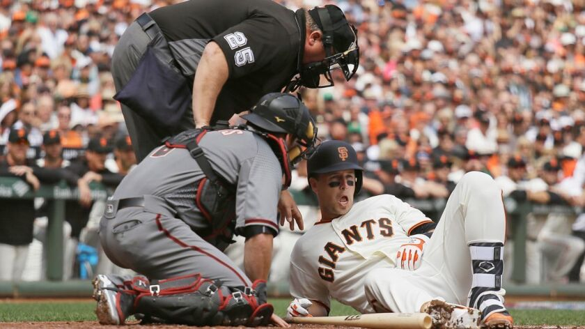 San Francisco Giants' Buster Posey, right, is looked at by home plate umpire Fieldin Culbreth and Ar
