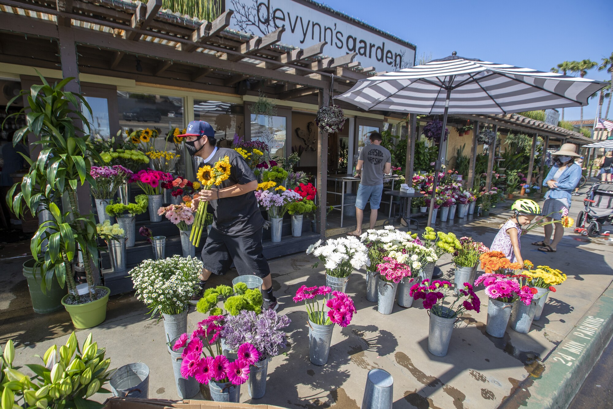 Employee Moy Ramirez, left, places flowers on display as Christina Dagle, right, and her daughter, Eleanor Eades, 4, buy flowers for a friend from Devynn's Garden in Seal Beach on Friday.
